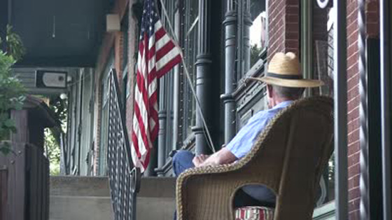 stock-footage-old-small-town-america-man-whittling-sitting-on-rocking-chair-american-flag-on-sidewalk-and-old