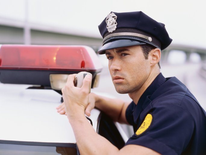 Side profile of a policeman using a radio