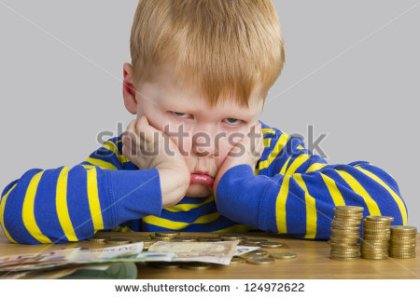 stock-photo-angry-boy-sitting-in-front-of-a-lot-of-money-124972622